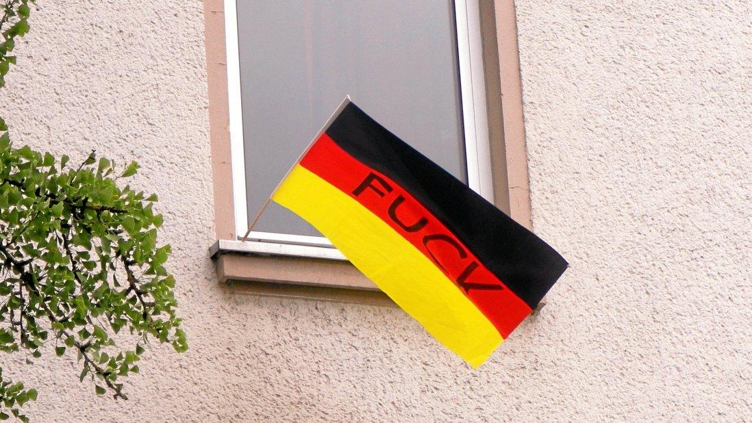 Beschmierte Deutschlandfahne aus dem Fenster des Asylbewerberheims gehängt