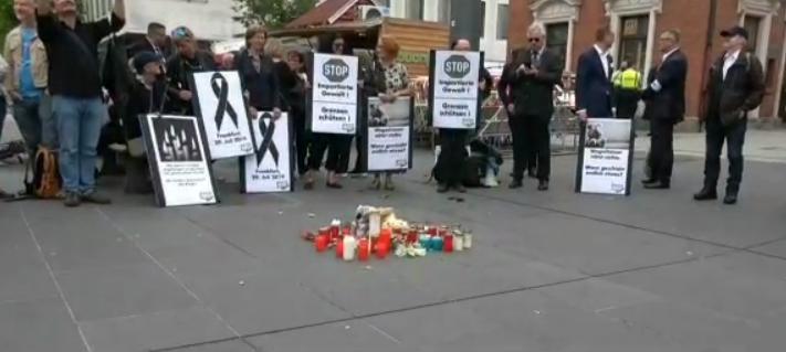 Linker schlägt auf Kamera während AfD-Mahnwache in München zu Bahnhofsopfern